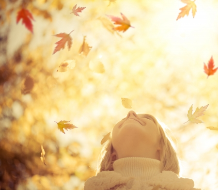 Happy child with maple leaves in autumn park against yellow blurred leaves background  Freedom concept