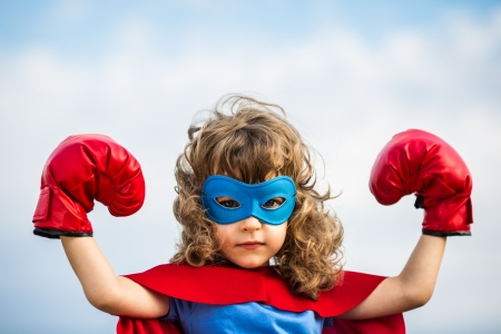 Superhero kid wearing boxing gloves against blue sky
