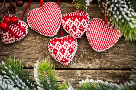Christmas tree decorations hanging on branch against wooden. Winter holidays concept