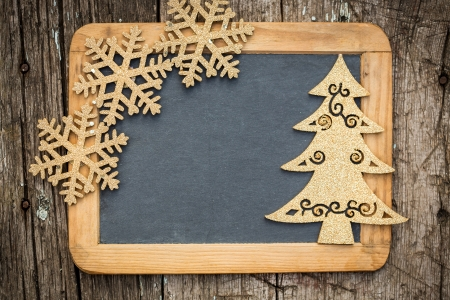 Gold Christmas tree decorations on vintage wooden blackboard with copy space  Xmas holidays card