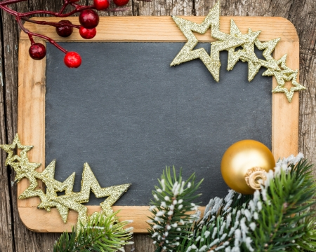 Vintage wooden blackboard blank framed in Christmas tree branch and decorations  Winter holidays concept  Copy space for your text