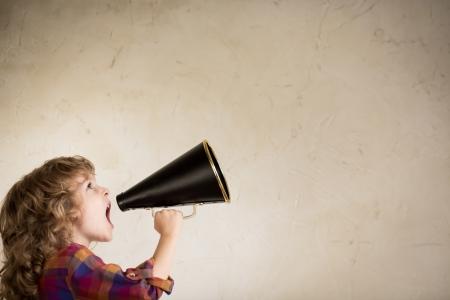 Kid shouting through vintage megaphone. Communication concept.
