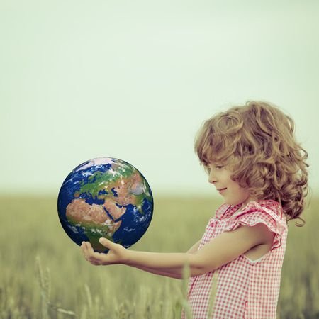 Child holding Earth in hands against green spring background.