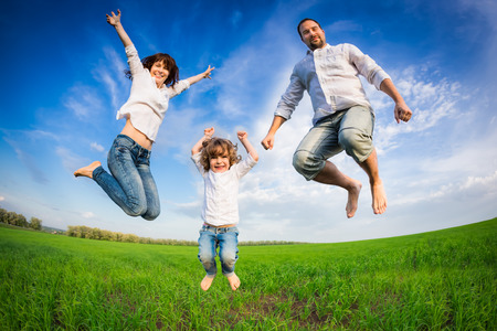 Photo pour Happy family jumping in green field against blue sky. Summer vacation concept - image libre de droit