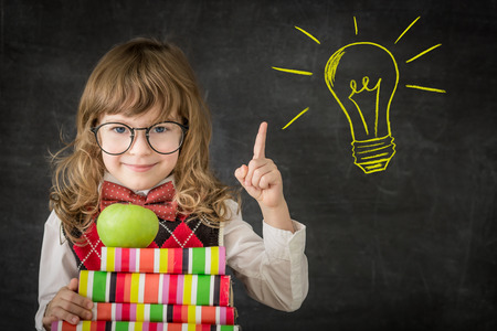 Smart kid in class. Happy child against blackboard. Drawing light bulb idea. Education concept
