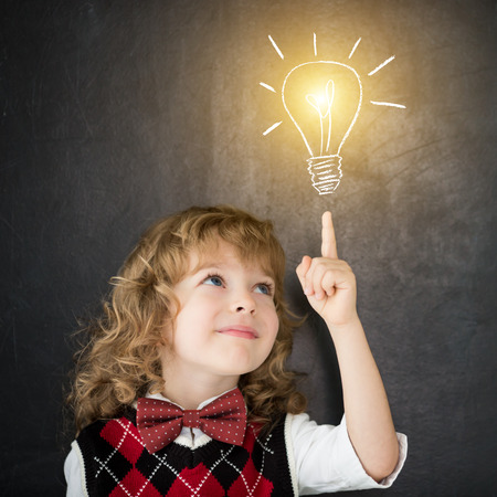 Photo for Smart kid in class. Happy child against blackboard. Drawing light bulb. Idea concept - Royalty Free Image