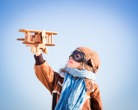 Happy kid playing with toy wooden airplane against winter sky background