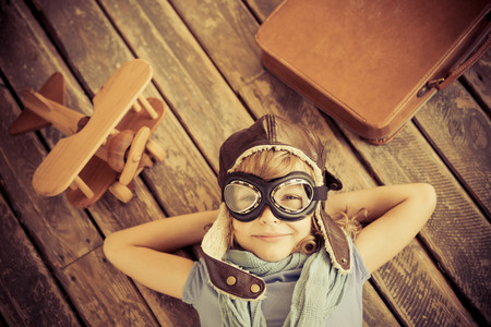 Foto de Happy child playing with toy airplane at home. Retro toned - Imagen libre de derechos