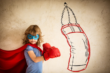 Superhero kid in red boxing gloves punching on the drawn bag. Winner and success concept