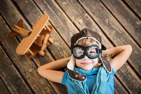 Photo for Child pilot with vintage plane toy on grunge wooden background - Royalty Free Image