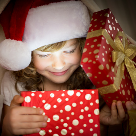 Child holding Christmas gift. Xmas holiday concept