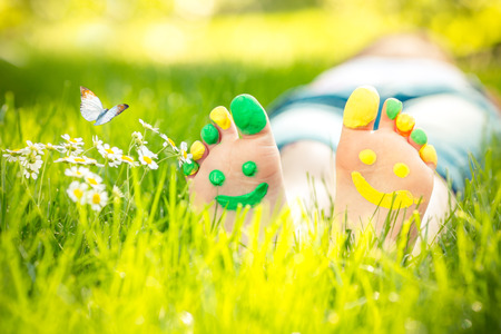 Photo pour Child lying on green grass. Kid having fun outdoors in spring park - image libre de droit