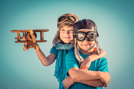 Foto de Happy kids playing with vintage wooden airplane outdoors. Portrait of children against summer sky background. Travel and freedom concept. Retro toned - Imagen libre de derechos