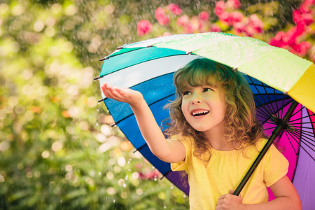 Happy child in the rain. Funny kid playing outdoors in spring parkの写真素材