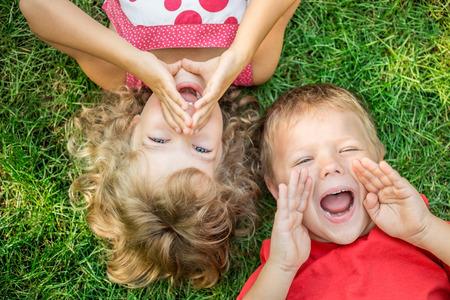 Foto de Funny kids shouting outdoors. Happy children lying on green grass. Communication concept - Imagen libre de derechos