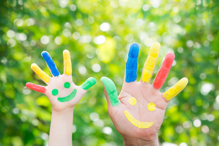 Smiley on hands against green spring background. Father and son having fun outdoors
