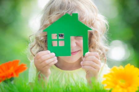 Happy child holding house in hands against spring green background. Real estate business concept