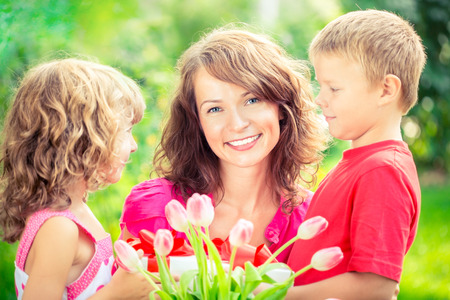 Photo for Happy family with bouquet of flowers and gifts outdoors. Young beautiful mother with son and daughter lying on green grass. Spring holiday concept. Women's day concept - Royalty Free Image
