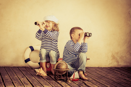 Foto de Children playing with vintage nautical things. Kids having fun at home. Travel and adventure concept. Retro toned image - Imagen libre de derechos