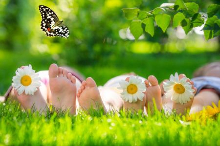 Foto de Happy family lying on green grass. Children having fun outdoors in spring park - Imagen libre de derechos