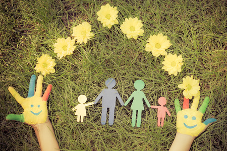 Group of happy people on green grass. Family having fun in spring. Smiley on hands. Ecology concept. Top view portrait. Retro toned image