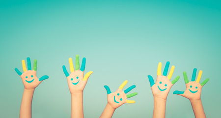 Happy people with smiley on hands against blue summer sky background