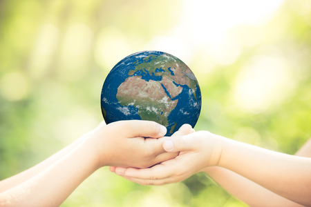 Children holding 3D planet in hands against green spring background. Earth day holiday concept. Elements of this image furnished by NASAの写真素材