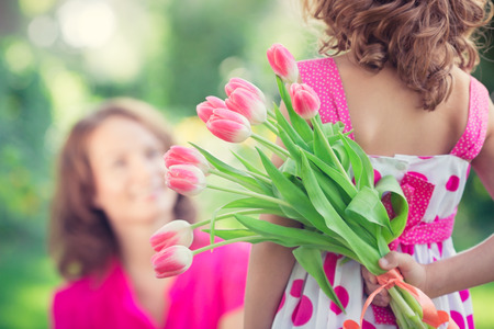 Woman and child with bouquet of flowers against green blurred background. Spring family holiday concept. Women's day