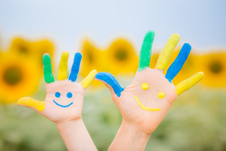 Photo for Happy family with smiley on hands against blue sky and yellow sunflower background - Royalty Free Image