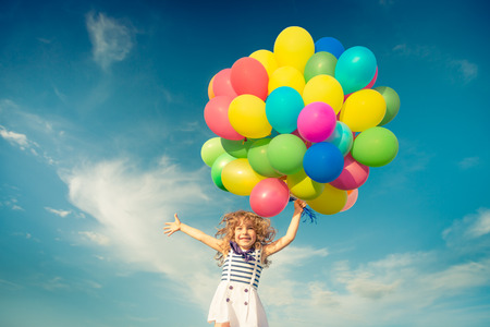 Photo pour Happy child jumping with colorful toy balloons outdoors. Smiling kid having fun in green spring field against blue sky background. Freedom concept - image libre de droit