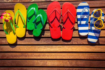 Multicolor flip-flops on wooden background. Summer family vacation concept