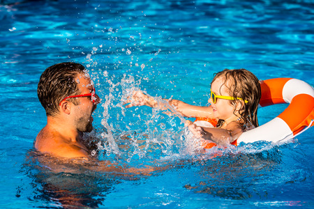 Foto de Happy child and father playing in swimming pool. Summer vacation concept - Imagen libre de derechos