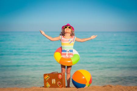 Foto de Happy child with vintage suitcase on the beach. Summer vacation and travel concept - Imagen libre de derechos