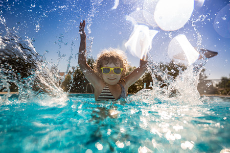 Foto de Happy child playing in swimming pool. Summer vacation concept - Imagen libre de derechos
