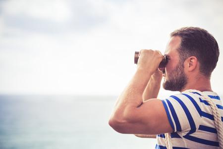 Sailor man looking through the binoculars against blue sky