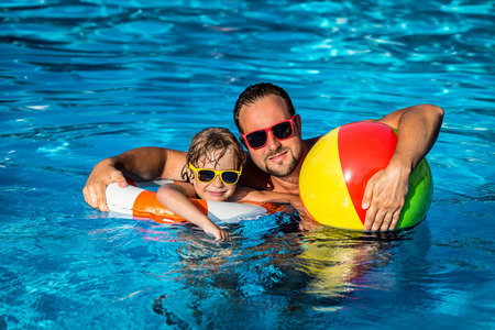 Photo for Happy child and father playing in swimming pool. Summer vacation concept - Royalty Free Image