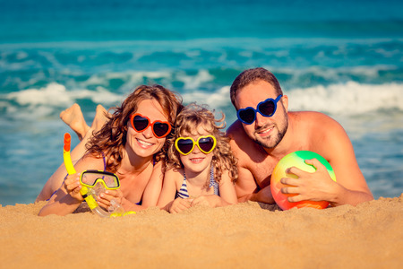 Foto de Happy family playing at the beach. Summer vacation concept - Imagen libre de derechos