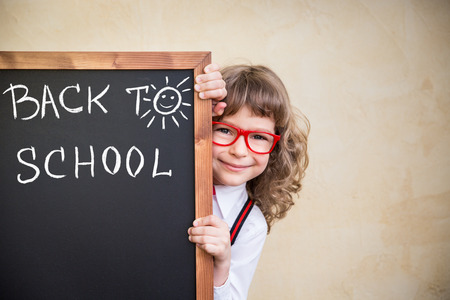 School kid in class. Happy child holding blackboard blank. Education concept
