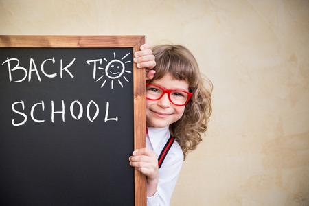 Foto de School kid in class. Happy child holding blackboard blank. Education concept - Imagen libre de derechos