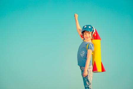 Foto de Happy child playing with toy rocket against summer sky background - Imagen libre de derechos