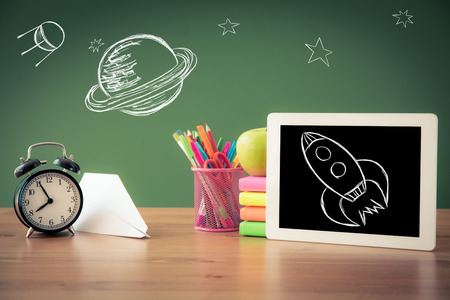 Tablet PC in classroom against green blackboard. Education concept
