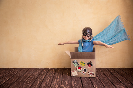 Photo for Happy child playing in cardboard box. Kid having fun at home - Royalty Free Image