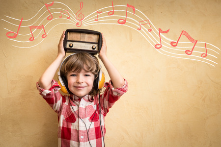Kid listen music at home. Hipster child with retro vintage radio