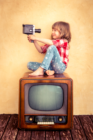 Child playing at home. Kid taking selfie with retro camera. Cinema concept
