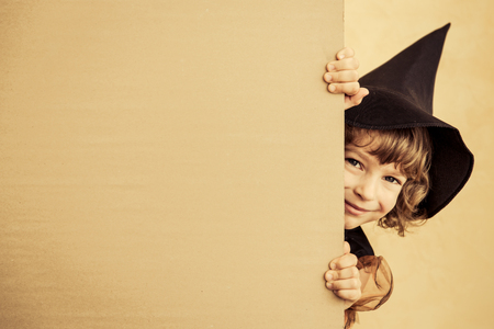 Funny child dressed witch costume. Halloween holidays concept