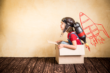 Photo pour Kid with jet pack. Child playing at home. Success, leader and winner concept - image libre de droit