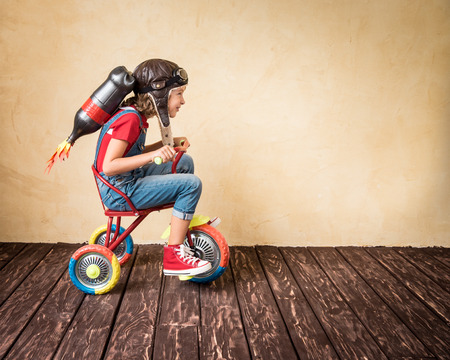 Foto de Kid with jet pack riding bike. Child playing at home. Success, leader and winner concept - Imagen libre de derechos