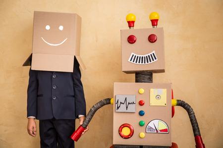 Foto de Portrait of young businessman with toy robot in modern loft office. Success, creative and innovation technology concept. Copy space for your text - Imagen libre de derechos