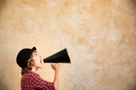 Kid shouting through vintage megaphone. Communication concept. Retro style