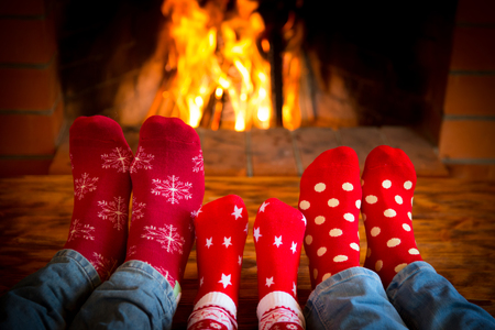 Family relaxing at home. Feet in Christmas socks near fireplace. Winter holiday concept